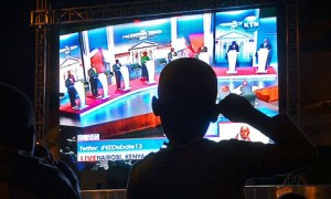 A boy watches the first presidential debate on a giant screen erected in a city park in Nairobi