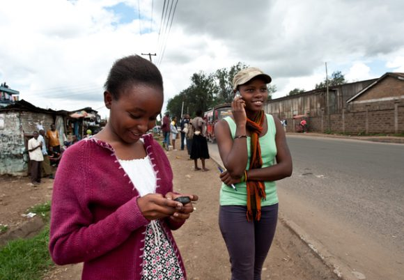 Connecting in Kenya: Two adolescents using their mobile phones.